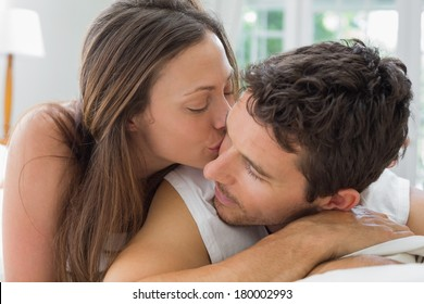Close-up of a young woman kissing man in bed at home