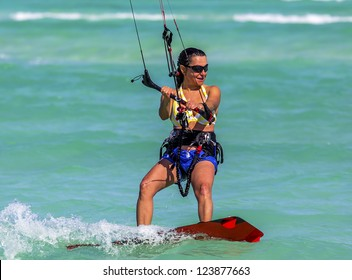 Close-up of a young woman kitesurfer riding in greenish-blue sea