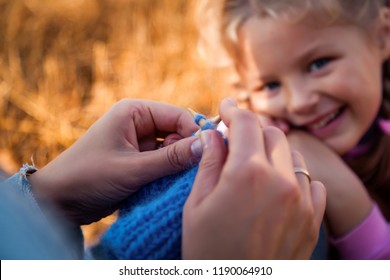 Close-up of a young woman knitting with her knitting blue cap made of natural wool, in the background a little daughter girl with blond hair smiles and watches mother work. The concept of livestyle
