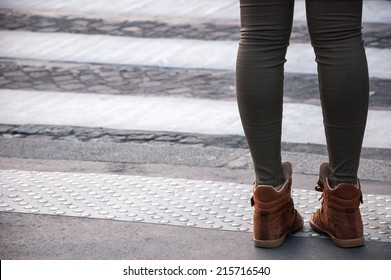 Closeup of young woman legs waiting at crosswalk.