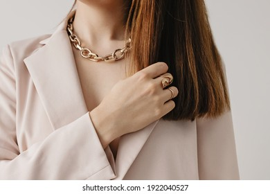 Close-up young woman in light beige jacket wearing golden chain necklace. Modern fashion details. Minimalist lifestyle
