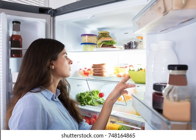 Close-up Of A Young Woman Looking At Fresh Food In Refrigerator