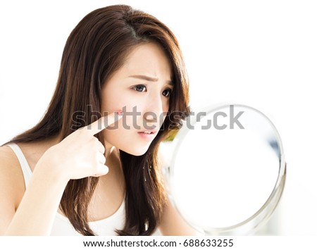 closeup of young woman looking into mirror