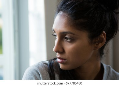 Close-up of young woman looking through window at home