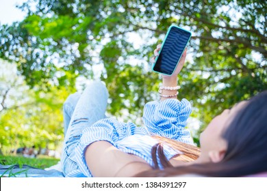 Closeup of young woman lying on the ground and using mobile with relax. Business and technology concept.