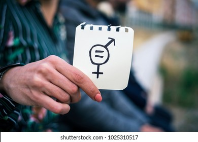 closeup of a young woman outdoors showing a piece of paper in front of her with a symbol for gender equality drawn in it