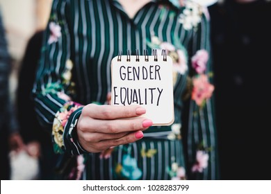 closeup of a young woman outdoors showing a notepad in front of her with the text gender equality written in it