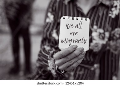 closeup of a young woman outdoors showing a notepad in front of her face with the text we all are migrants written in it, in black and white