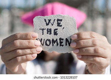 closeup of a young woman outdoors wearing a pink pussycat hat showing a piece of paper in front of her face with the text we the women written in it