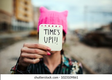 closeup of a young woman outdoors wearing a pink pussycat hat showing a piece of paper in front of her face with the text time is up written in it