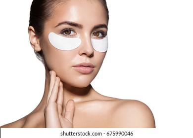 Close-up of a young woman with patches under eyes from wrinkles and dark circles. Isolated on white background