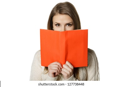 Closeup of young woman peeking over the edge of the opened book, looking at camera, over white background