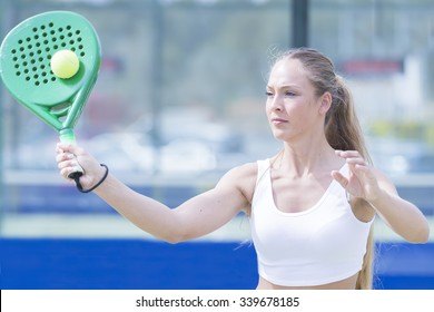 closeup of a young woman playing a paddle match is hitting ball in an artificial grass court outdoor - focus on the face