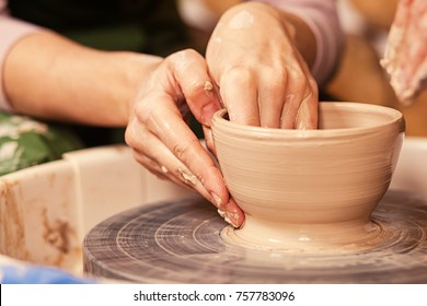 Close-up of a young woman potter sculpting on a potter's wheel a vase made of brown clay, makes a smooth edge at the bowl in the creative workshop, side view