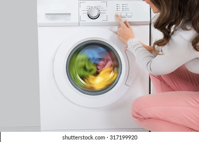 Close-up Of Young Woman Pressing Button Of Washing Machine In Kitchen