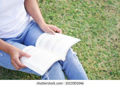 Closeup young woman reading a book sitting on green grass with relax feelling