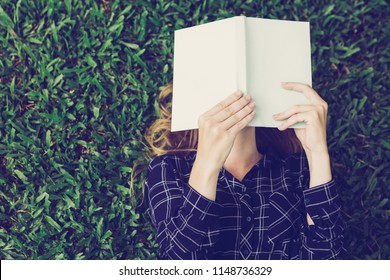Closeup of young woman reading book, covering her face with it and lying on grass in park. Top view.
