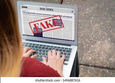 Closeup of young woman reading digital fake news on laptop. Propaganda and disinformation online. Media and digital concept. All screen graphics are made up by us