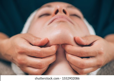 Close-up of a young woman receiving chin and jawline face lifting massage