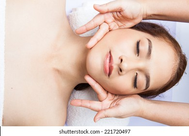 Close-up of young woman receiving facial massage at day spa