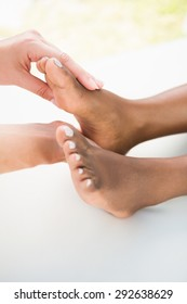 Close-up of a young woman receiving foot massage at spa center
