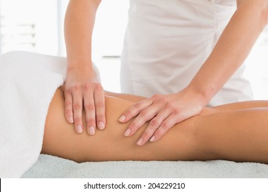 Close-up of a young woman receiving leg massage at spa center