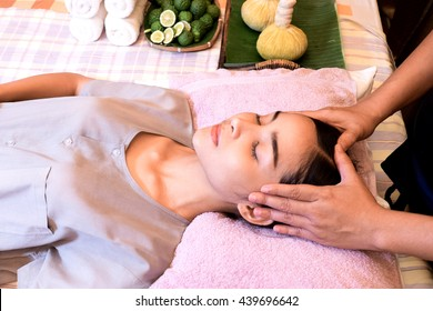 Closeup of a young woman receiving a relaxing head massage in a spa center