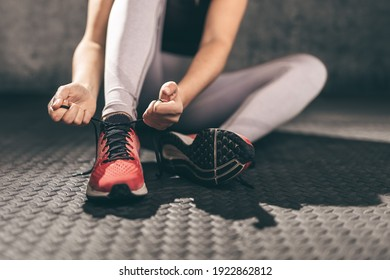 Closeup of young woman runner tying her shoelaces.