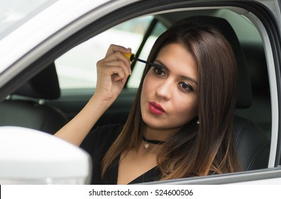 Closeup young woman sitting in car putting on makeup looking in mirror, as seen from outside drivers window, female driver concept