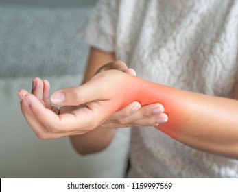 Closeup young woman sitting on sofa holds her wrist. hand injury, feeling pain. Health care and medical concept.