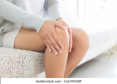 Closeup young woman sitting on sofa and feeling knee pain and she massage her knee at home. Healthcare and medical concept.