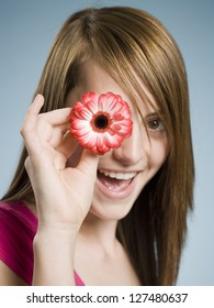 Close-up of young woman smiling and holding flower up to her eye over gray background
