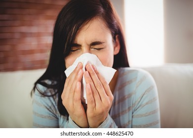Close-up of young woman sneezing at home