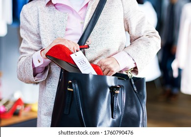 Closeup of young woman is stealing red shoes in store, shop, boutique at shopping center. Girl thief is hiding unpaid good in handbag while seller, assistant turned away. Shoplifting concept.