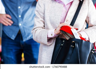Closeup of young woman is stealing red shoes in store, shop, boutique at shopping center. Girl is hiding unpaid good in handbag. Seller, assistant caught thief on hot. Shoplifting concept.