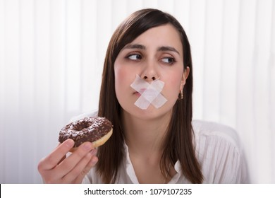Close-up Of A Young Woman With Sticky Tape Over Her Mouth Unable To Eat Donut