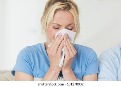 Closeup of a young woman suffering from cold with eyes closed