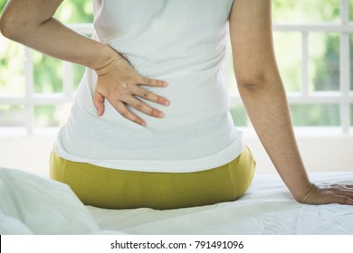 Closeup of young woman suffering from pain back while sitting on bed at home, People with body-muscles problem, Healthcare And Medicine concept
