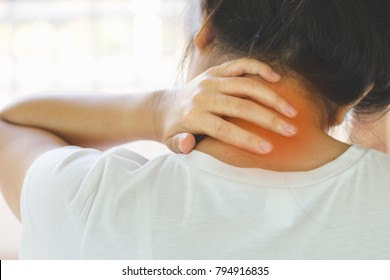 Closeup of young woman suffering from pain in neck while sitting on bed at home, People with body-muscles problem, Healthcare And Medicine concept