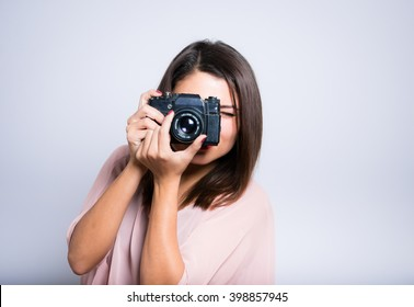 closeup of a young woman taking pictures on vintage camera