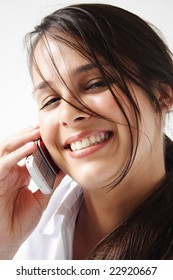 Closeup of a young woman talks and smile on cellphone.