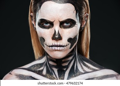 Closeup of young woman with terrifying skeleton makeup over black background