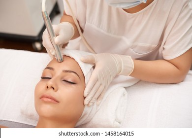 Close-up of a young woman with a towel on her head lying on a table with closed eyes getting a laser skin treatment in healthy beauty spa salon