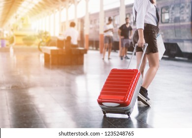 Close-up of young woman traveler carrying her trolley red bag and map in a train station.