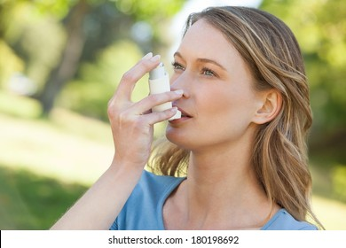 Close-up of a young woman using asthma inhaler in the park