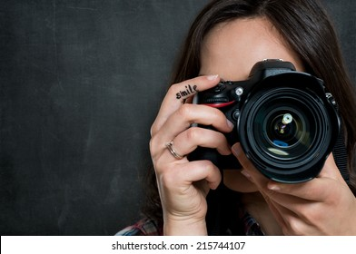 Closeup Of Young Woman Using Camera Over Gray Background