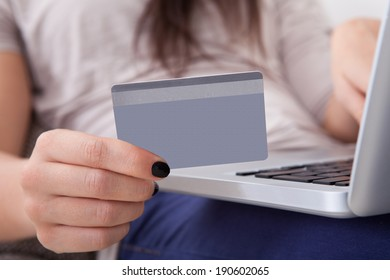 Close-up of young woman using credit card and laptop to shop online at home