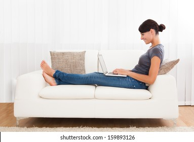 Close-up Of Young Woman Using Laptop On Couch