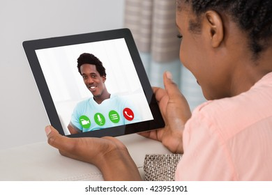 Close-up Of A Young Woman Video Conferencing With Man On Digital Tablet