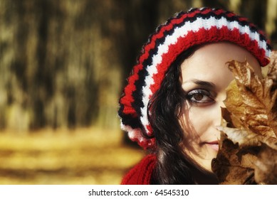 Closeup of young woman in woven hat with yellow leaves and blurred background with copy space
